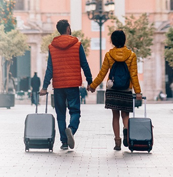 A man and woman hold hands while rolling luggage down the street